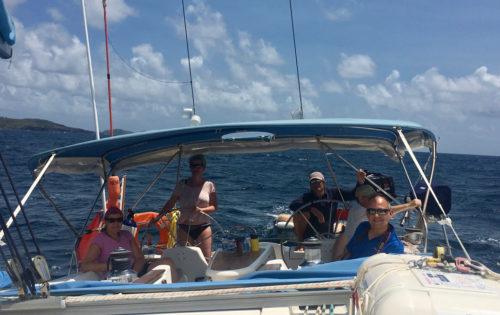 BlueFoot Travel guests on the helm as we sail around Ronde Island to Grenada
