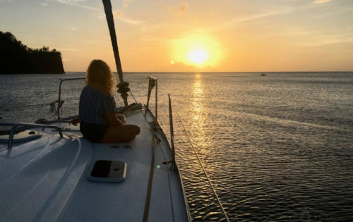 A BlueFoot Travel guest enjoying one of the stunning sunsets in Cumberland Bay on Nemo's bow