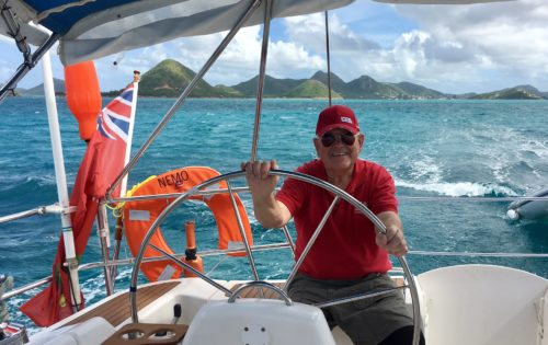 BlueFoot Travel guest Don at the helm under guidance from Skipper Neil in Antigua & Barbuda